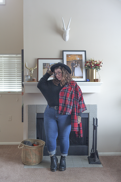 An outfit consisting of a wide brim black hat, a black sweater half tucked into a pair of mid rise blue jeans, a red plaid moto jacket and black chelsea boots.