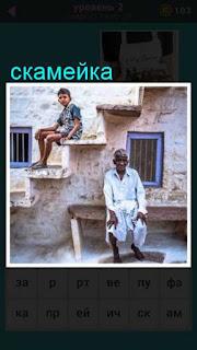 около дома на скамейке сидит пожилой мужчина, а рядом мальчик смотрит