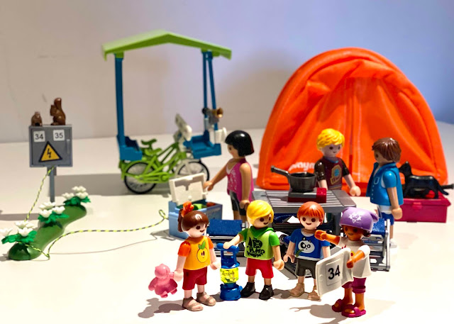 a scene set up with PLAYMOBIL children standing in a group in the foreground with adults cooking food on a camp stove behind and a tent and family bicycle in the background