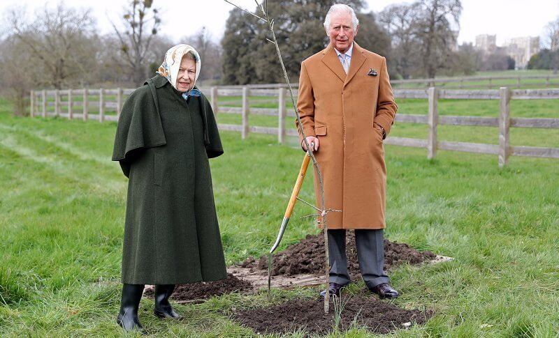 Queen Elizabeth wore a dark green coat with caped detailing and a patterned silk scarf