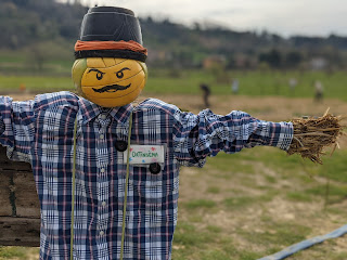 A scarecrow advertises Ortinsema - a project of shared gardening.