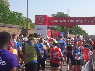 Runners walking over the red start line of the London Marathon
