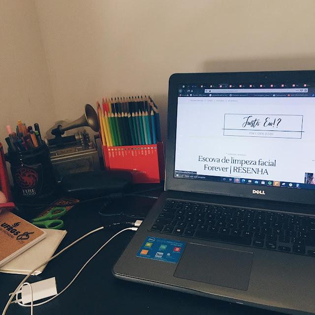 foto da minha mesa de trabalho, a mesa é preta, em cima dela está o notebook com a página do blog aberta, minha caixinha de jóias que também é uma caixinha de música, meu lápis de cor, minhas canetas