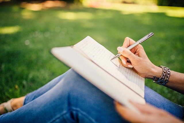 Mulher sentada em uma área verde, ao ar livre escrevendo