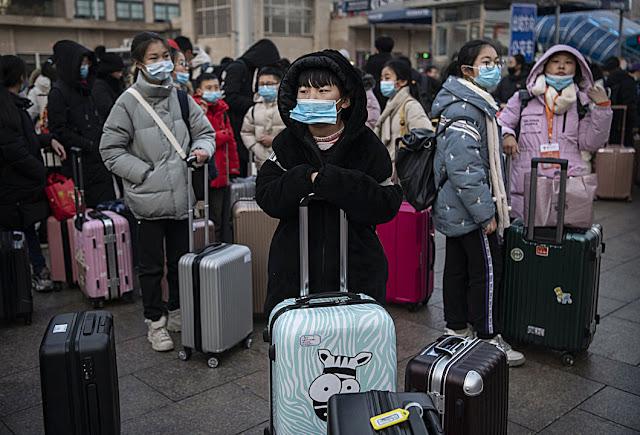 Regime  socialista silenciou o surto e agora o país ficou sem rumo. Crianças aguardam poder pegar em trem em Pequim.