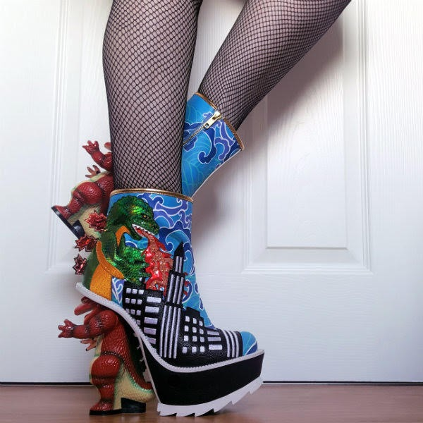 leg lifted showing fire breathing dino on side of boot and dinosaur shaped heel