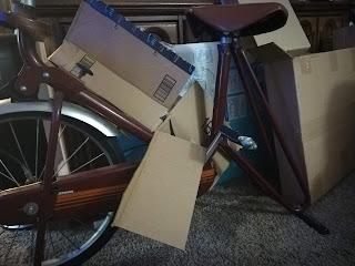 multiple cardboard boxes surrounding a vintage exercise bike