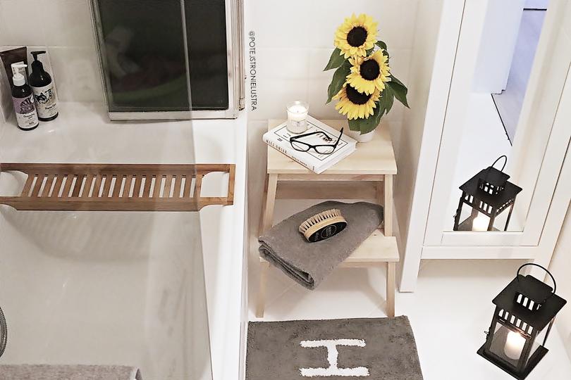 przytulna biała łazienka z drewnianą półką na wannie