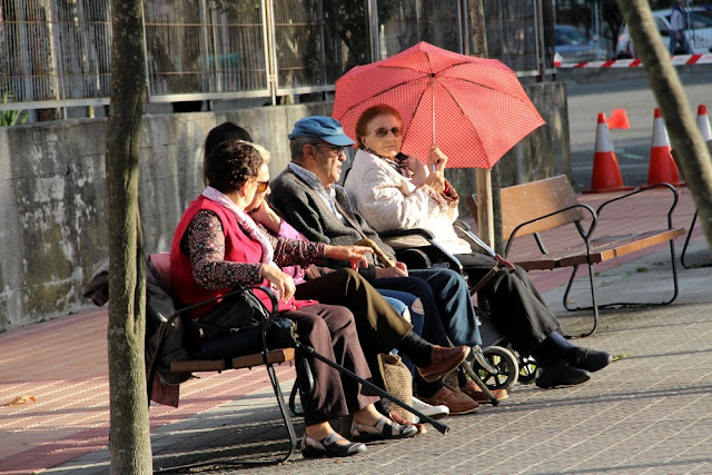 Ancianos toman el sol en un banco