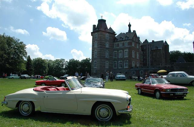 weisser Oldtumer und roter Mercedes Benz SL 560 parken auf der grünen Wiese auf Schloss Merode