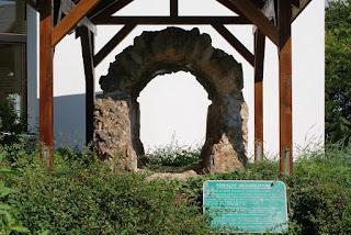 Ein Stück der Römischen Wasserleitung. Eine Ovale Röhre aus Stein mit geradem Boden. Sie steht unter einem hölzernen Dach