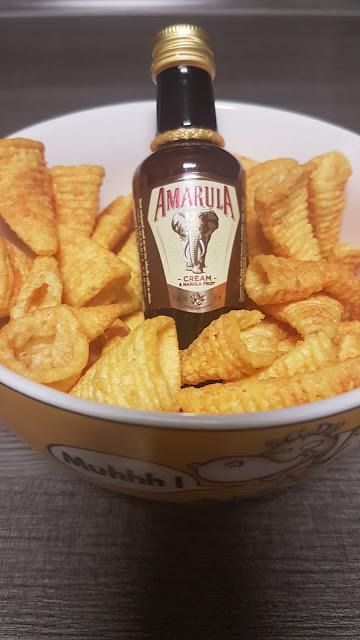 eine 0,05l Creamlikör Amarulaflasche serviert mit Chips