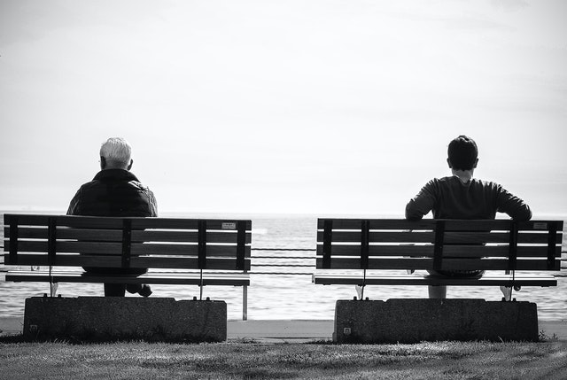 man and woman seated on a bench waiting