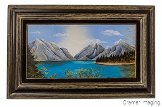 Cramer Imaging's photograph of a framed landscape painting with mountains and a lake on a white wall