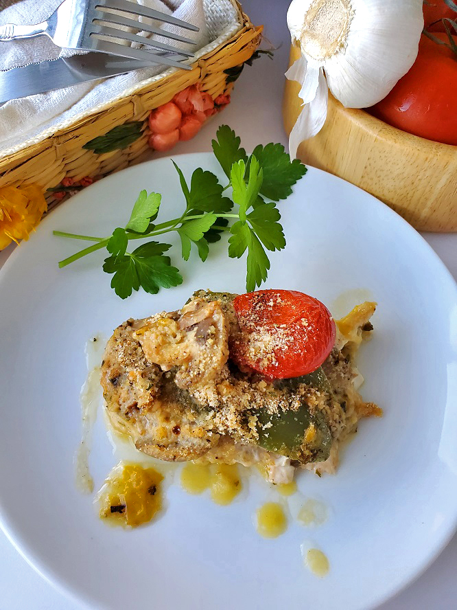 baked chicken on a white plate with mushrooms, peppers and tomatoes sprinkled with panko breadcrumbs