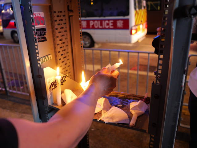 placing a lit candle with a police vehicle in sight