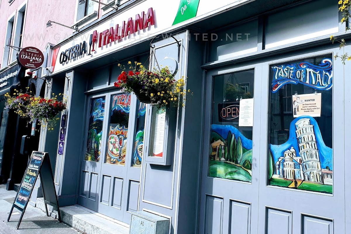 Shopfront in Galway city painted with stereotypical Italian mems including the leaning tower of pizza.   Also hanging baskets of red and yellow flowers.