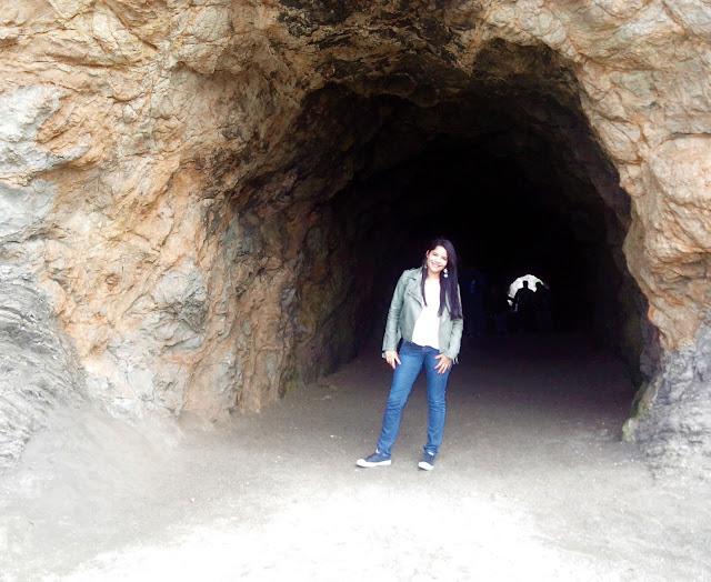 mulher no meio da entrada para uma caverna