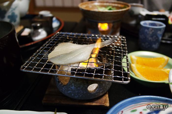 poisson qui grille sur la flamme d'un brasero