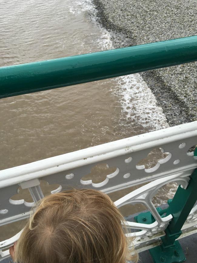 Penarth-pier-toddler-looking-at-sea-through-railings