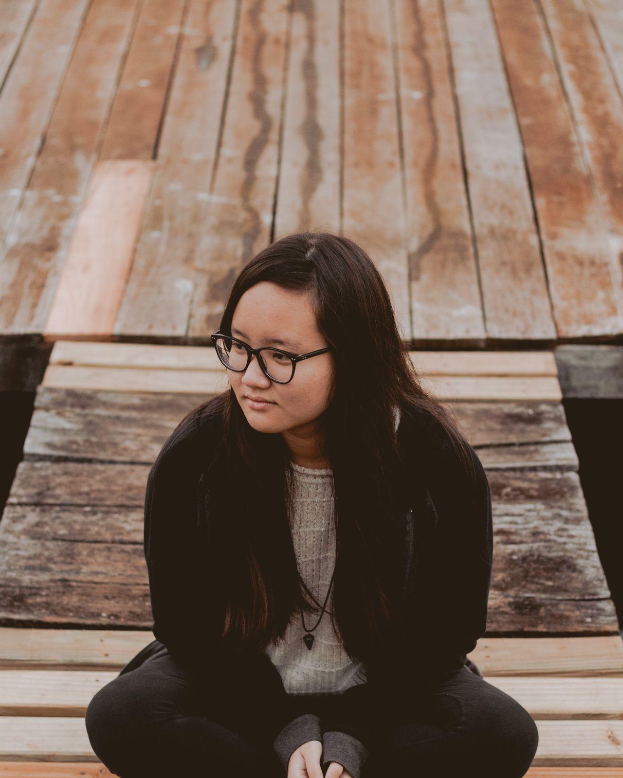 adolescente sentada piso madeira