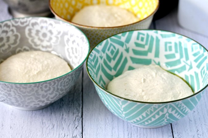 Pizza dough in bowls rising