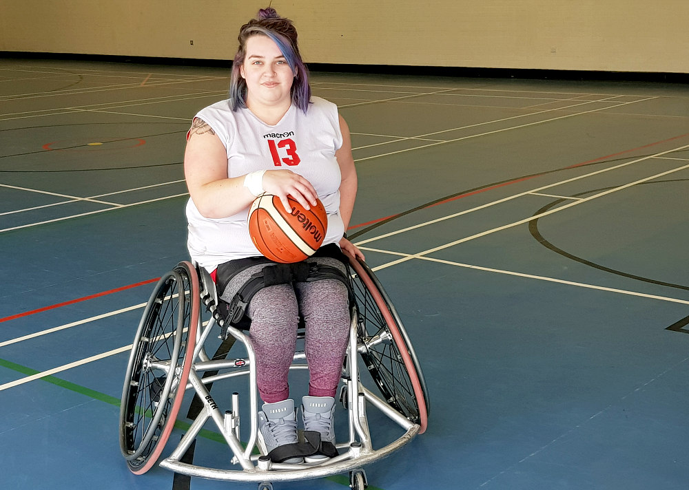 Beth is sat in a silver basketball wheelchair. She is wearing a white vest with the number 13 on it, grey and burgundy leggings and grey trainers. She is holding a ball on her lap and is looking directly at the camera