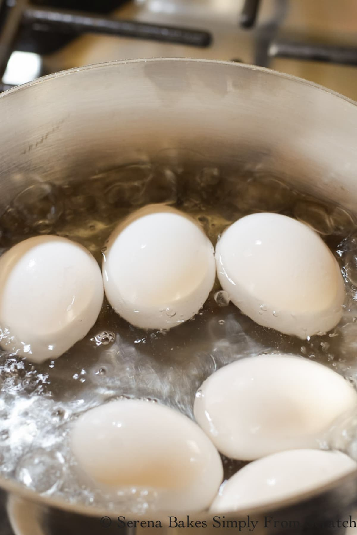 6 Eggs in watering boiling half way up their sides in a large pot.