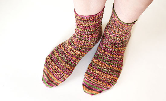 Feet standing casually wearing socks knit in autumn colors on a white background.