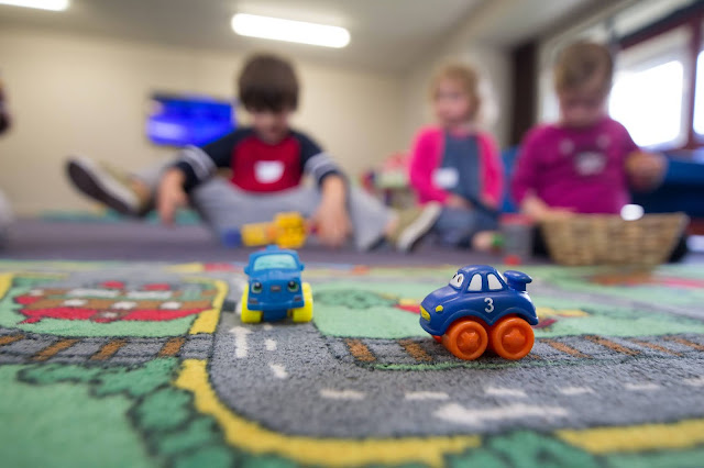 Children at pre school with toy cars in foreground:Photo by BBC Creative on Unsplash