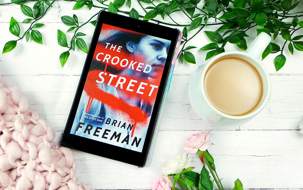 Kindle fire showing the The Crooked Street by Brian Freeman cover. Theres leaves, a pink blanket and roses in the background