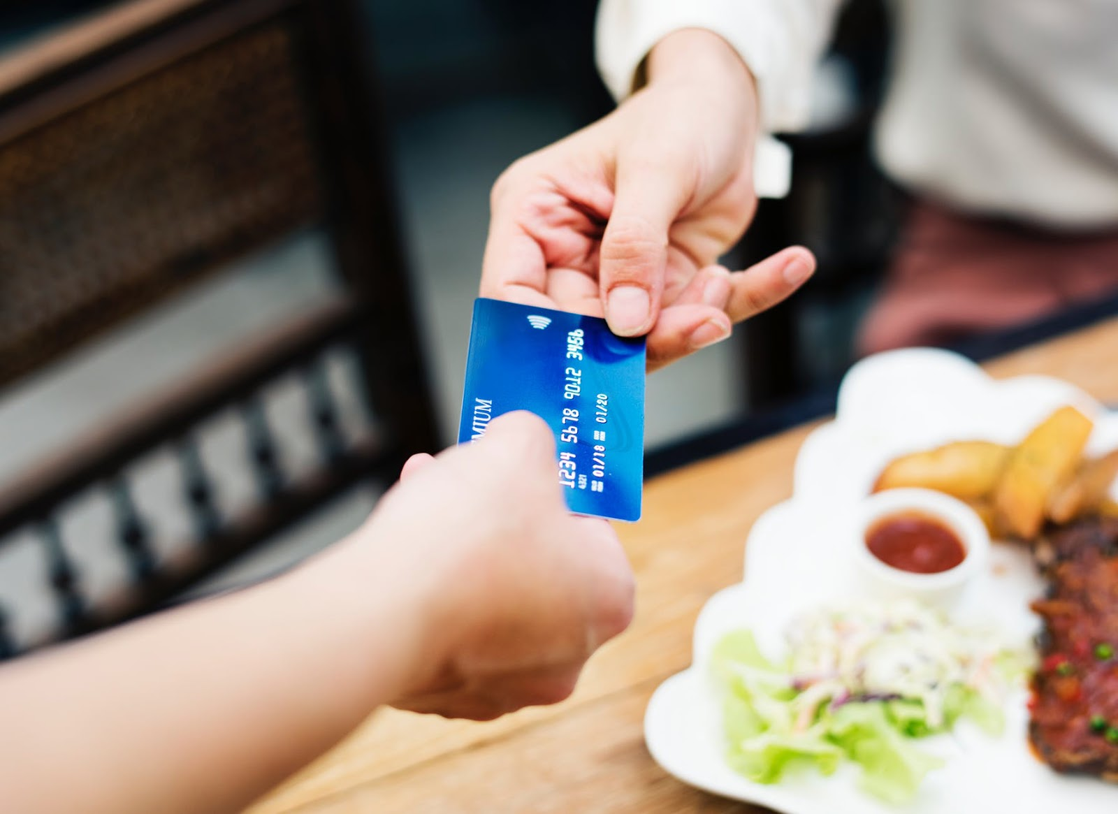 a person handing over a debit card to a basic bank account