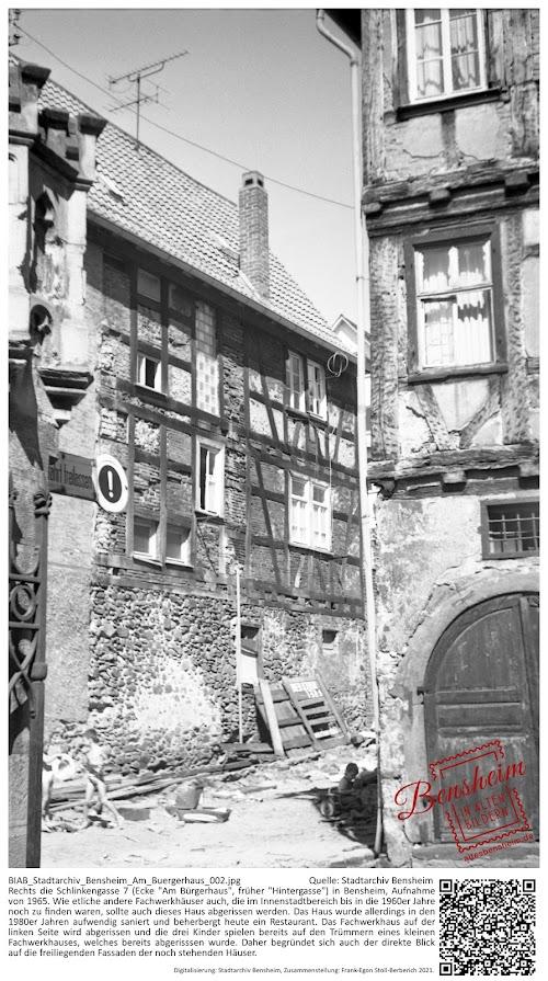 """BIAB_Stadtarchiv_Bensheim_Am_Buergerhaus_002.jpg; Quelle: Stadtarchiv Bensheim Rechts die Schlinkengasse 7 (Ecke """"Am Bürgerhaus"""", früher """"Hintergasse"""") in Bensheim, Aufnahme von 1965. Wie etliche andere Fachwerkhäuser auch, die im Innenstadtbereich bis in die 1960er Jahre noch zu finden waren, sollte auch dieses Haus abgerissen werden. Das Haus wurde allerdings in den 1980er Jahren aufwendig saniert und beherbergt heute ein Restaurant. Das Fachwerkhaus auf der linken Seite wird abgerissen und die drei Kinder spielen bereits auf den Trümmern eines kleinen Fachwerkhauses, welches bereits abgerisssen wurde. Daher begründet sich auch der direkte Blick auf die freiliegenden Fassaden der noch stehenden Häuser."""