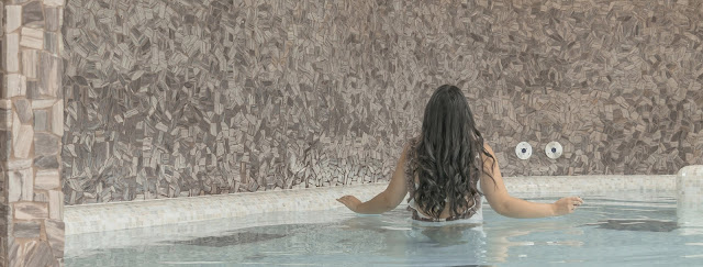 a girl stands waist-deep in a crystal clear indoor pool.
