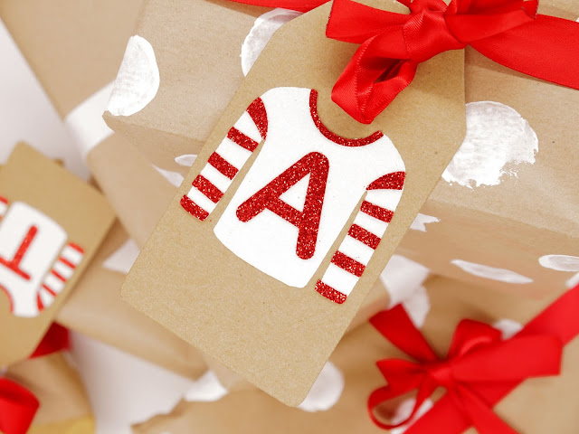 a shot taken from above but angled to the right, of presents wrapped in brown kraft paper, tied with white ribbons. Some have white spots and red ribbons. On the top present is a kraft tag with a white glitter christmas jumper stuck on it, with red stripes stuck on the sleeves and a red A on the chest.