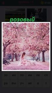 в середине розовой аллеи сидит девушка с собакой