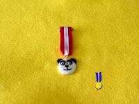 Foto de medalla en fimo de la cara de un Oso Panda