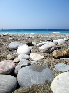 Beautiful Greek beach, pebbly beach and turquoise sea. Mediteranean sea in summer. A summer beach holiday in Europe.