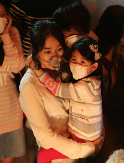 Woman in mask carrying little girl in mask