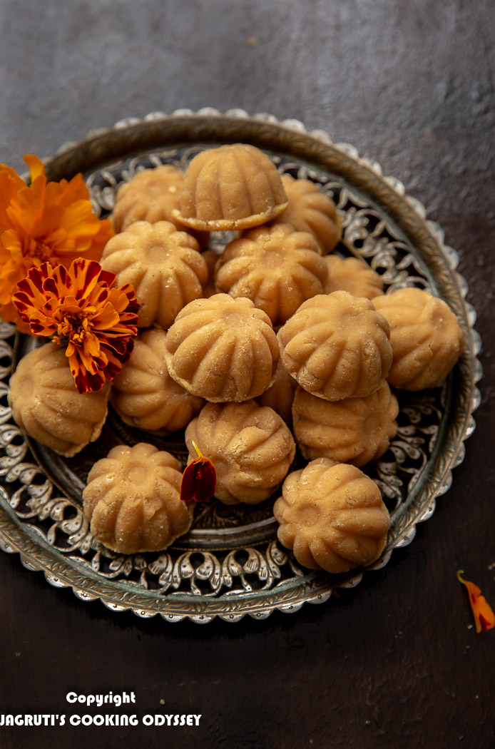 Mawa peda arranged on a beautiful vintage plate with two orange marigold flowers.