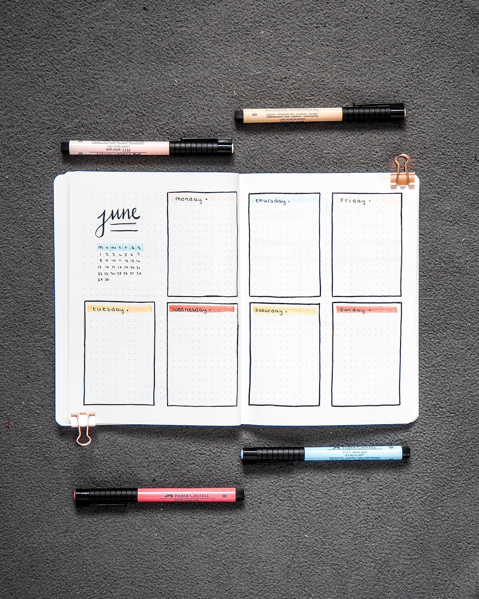 a double spread of a weekly spread out. each page spilt into four, with the top left showing a mini month calendar, and then the rest of the quadrants for each day of the week