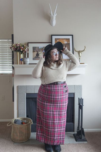An outfit consisting of a black wide brim hat, a cream cowl neck sweater tucked into a maxi pink plaid skirt.