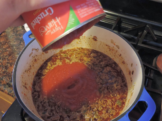 Tomato puree being added to the pot.
