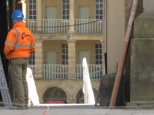 Worker in blue hard hat stands at Piece Hall entrance (Halifax) during restoration.