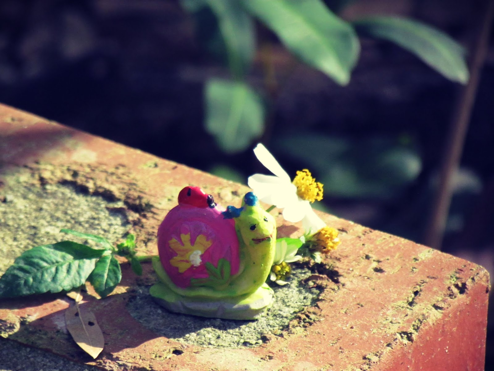 A brick manmade garden in Hammock Park With Soil, green leaves, wild daisies, and a faux garden snail in the sunlight