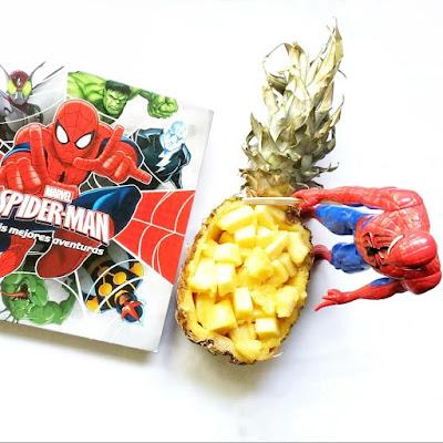 Un libro de Spiderman y una figura de spirden acompañan una piña a la mitad vaciada y rellena de cubos de piña