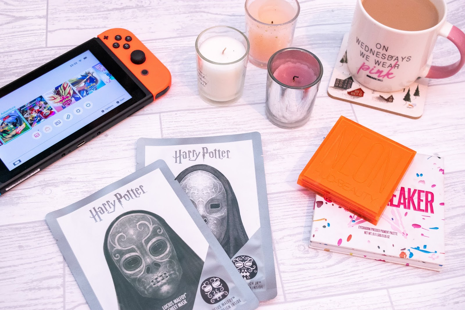 A flat-lay including a Nintendo Switch to the top right, two Harry Potter themed face masks at the bottom stacked, three votive candles in pink, white and lilac, a cup of tea in a white and pink mug on the top right and two eye-shadow palettes on the bottom left stacked one on top of the other.