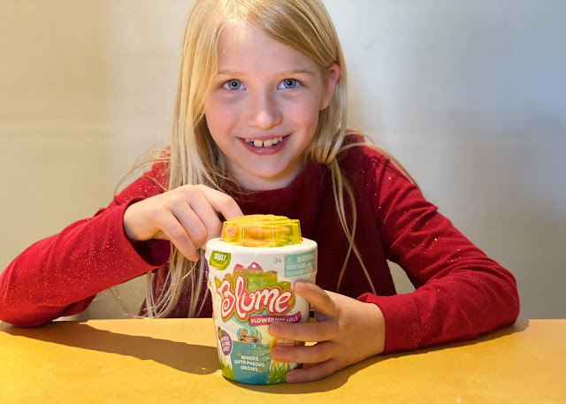 A smiling girl about to open Blume Dolls Series 2 pot which has a yellow lid