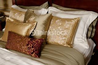 Spalnica. Okrasne blazine na postelji.