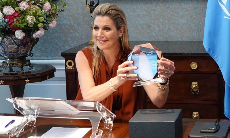 Queen Maxima wore a brow silk sleeveless tie-bow blouse from Natan. black diamond earrings. EMERGE Financial Health conference